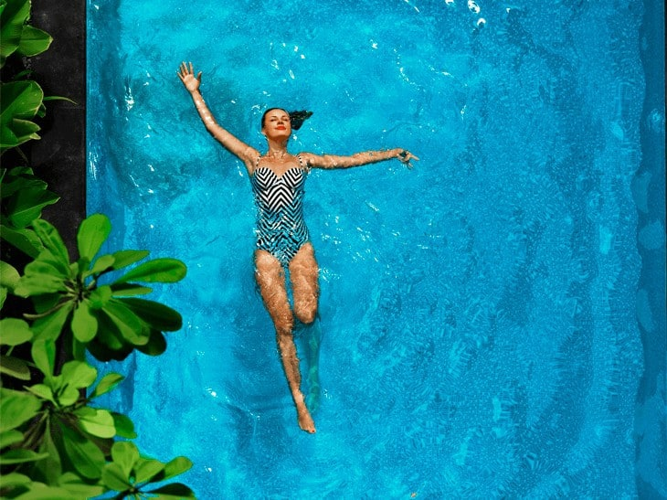 Overhead shot of a lady in striped swimsuit floating lazily in a pool