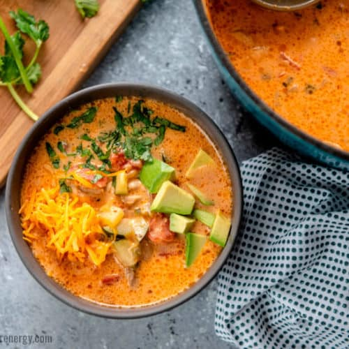 Overhead shot of Chicken Taco Soup in grey bowl with ladle, avocado and tomatoes