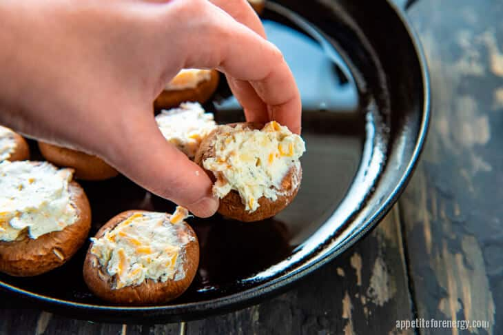 A hand placing stuffed mushrooms on skillet ready to cook