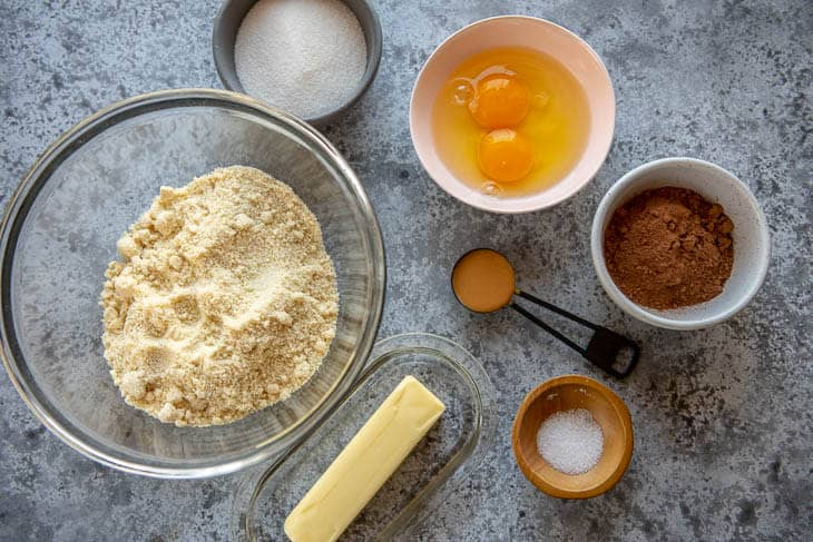 Almond flour, sweetener, butter, cocoa powder, eggs, peanut butter and salt in bowls