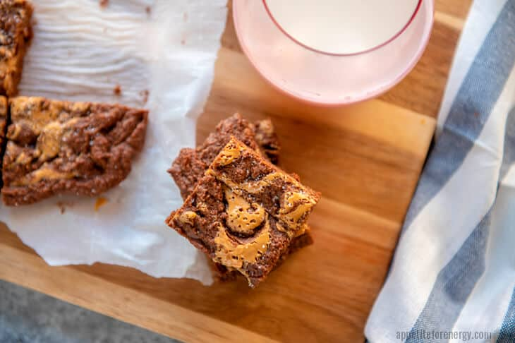 A stack of Keto Peanut Butter Brownies on a wooden board with glass of almond milk