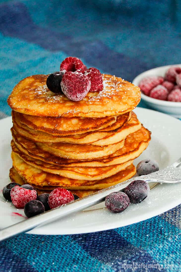 A delicious stack of golden pancakes on a plate with raspberries and blueberries scattered around