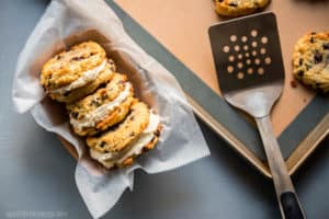 Keto Chocolate Chip Cookie Sandwiches arranged in a tray with parchment paper and a spatula