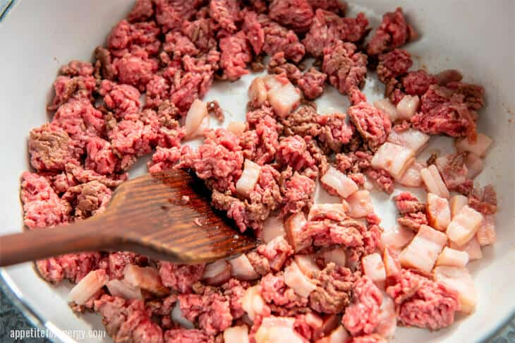 Cooking ground beef with bacon in a white pan with wooden spoon