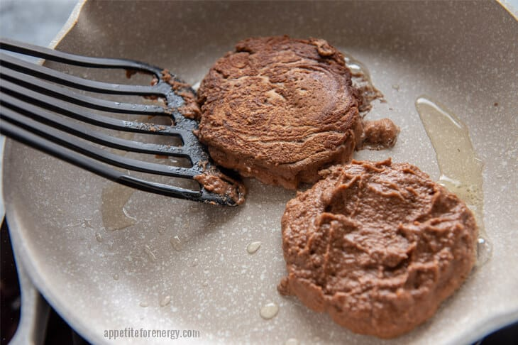 Flipping the protein pancakes with black spatula in a white skillet