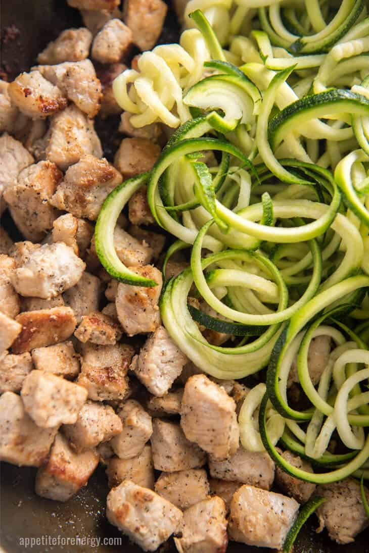 Zoodles and pork sautéing in skillet