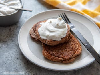 Chocolate Protein Pancakes on a white plate smothered in cream, with a fork
