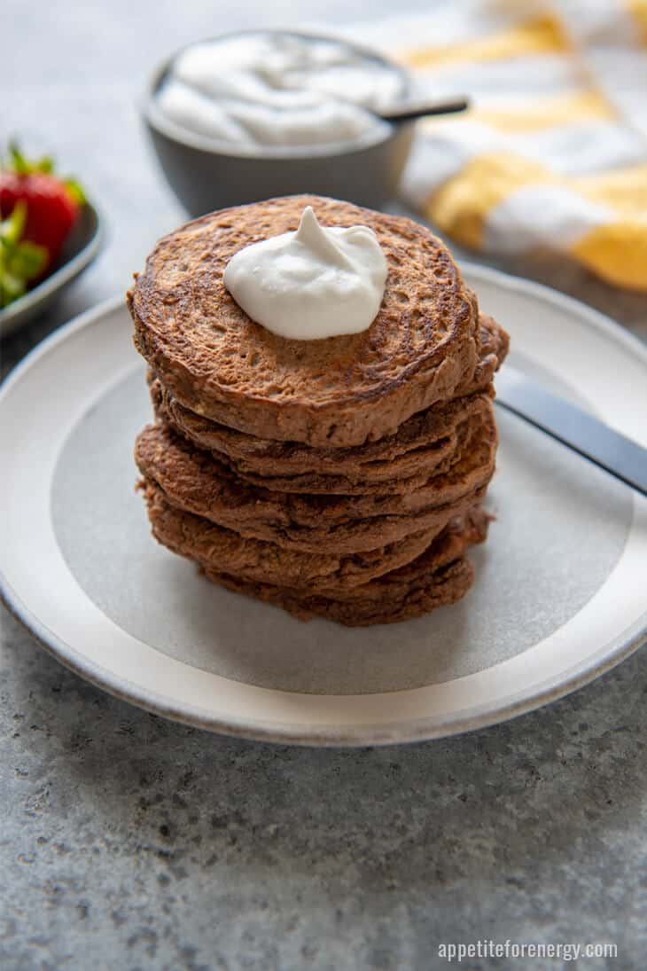 A Stack of Keto Chocolate Protein Pancakes on a white plate with sloop of cream and fork