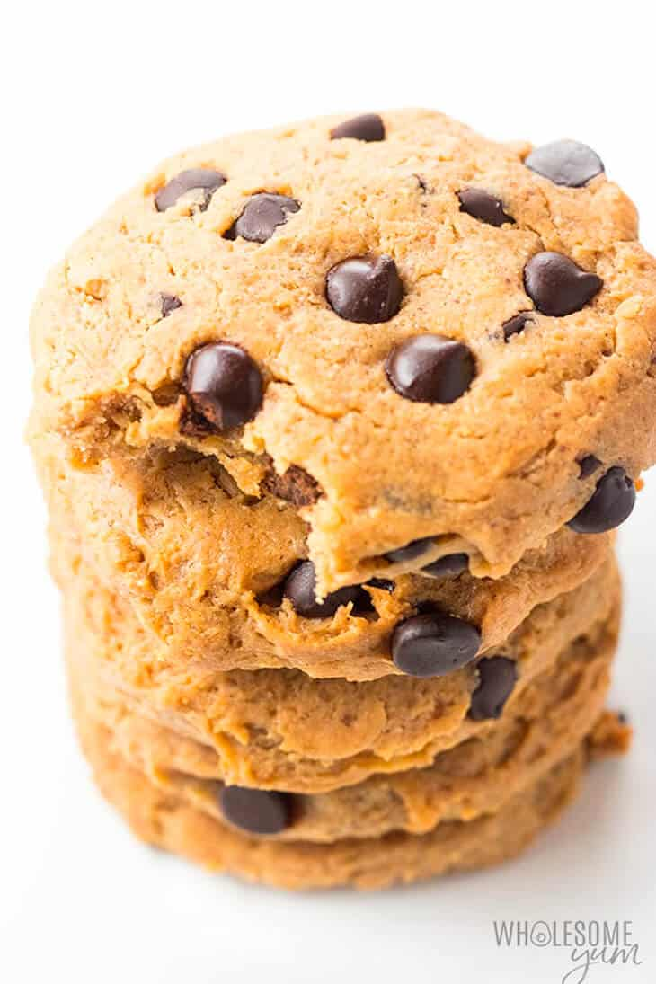 A big stack of chocolate chip cookies with a bit taken out of the top cookie