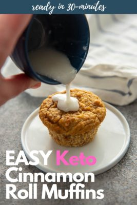 Pouring frosting from blue bowl onto low carb cinnamon muffin on a white plate