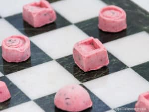Keto ice cream bites on the white squares of a chess board