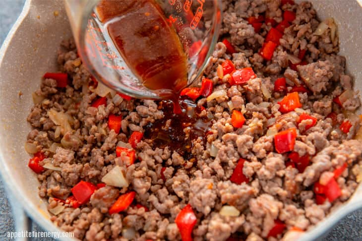 Pouring sauce onto pork mixture in large sklllet
