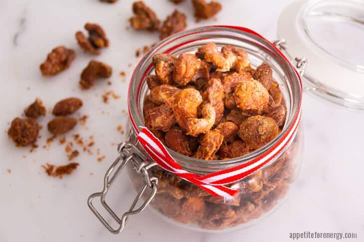 Keto spiced nuts in a glass jar with red and white striped ribbon around jar