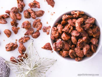 Spiced Nuts in a white bowl and spilled on the white counter with Christmas star