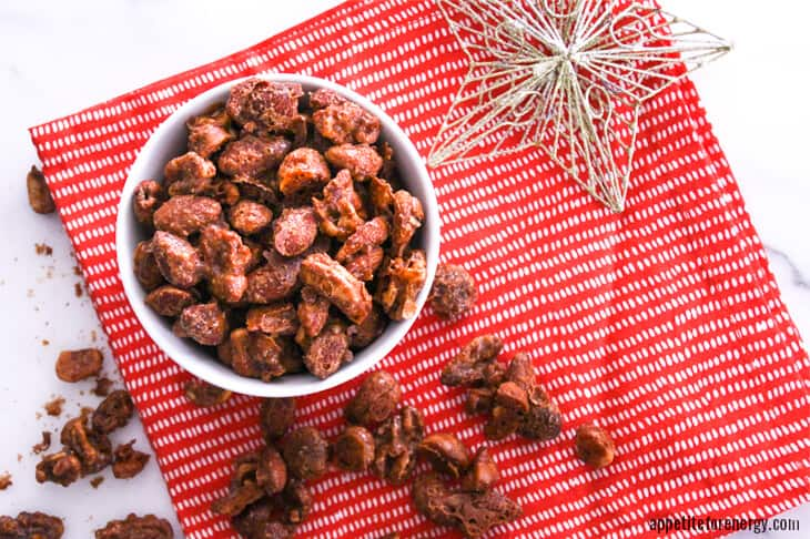 Cinnamon-Maple Spiced Nuts in white bowl on red napkin with Christmas star