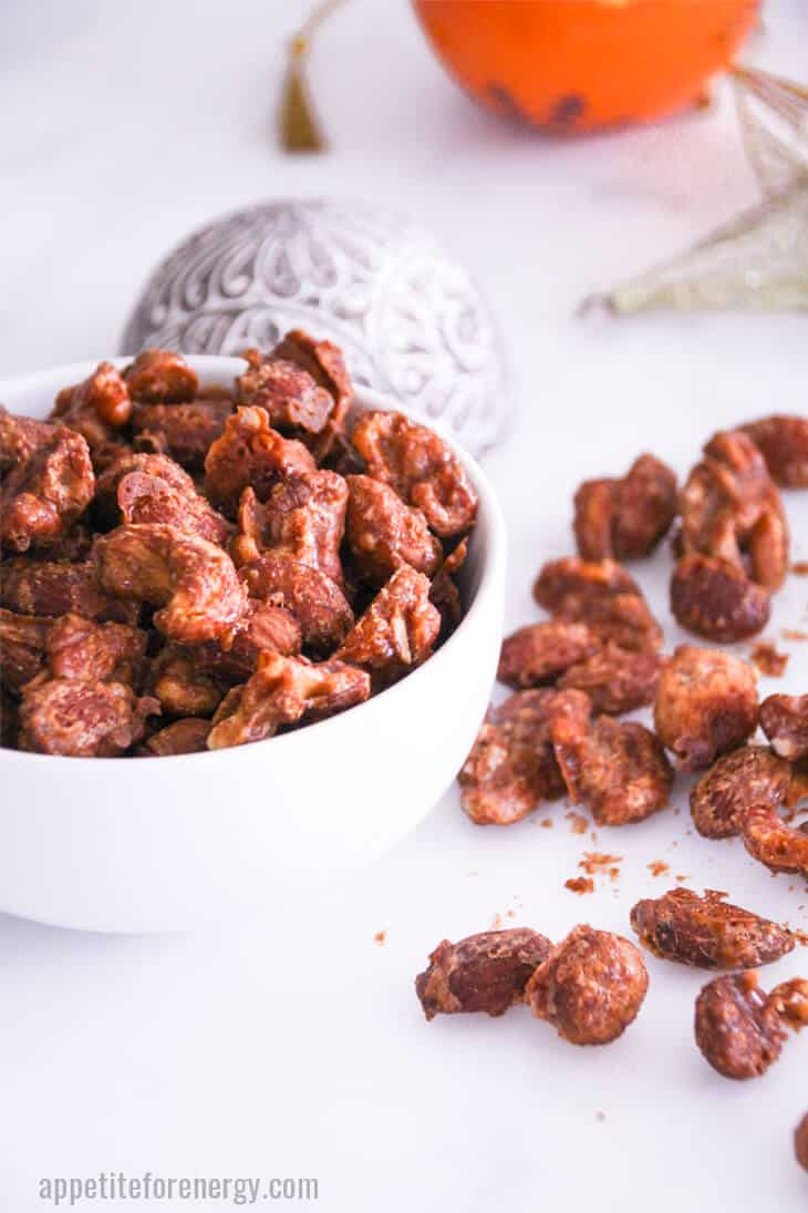 Easy Keto Cinnamon-Maple Spiced Nuts in white bowl with Festive decorations