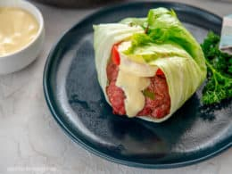 Lettuce wrapped pork burger with sauce drizzled over on blue plate