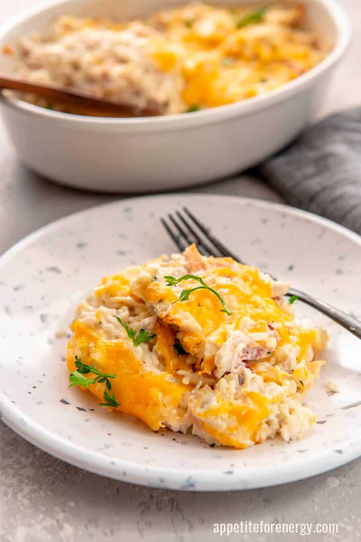 A serving of KETO Chicken Cauliflower Rice Casserole on a white plate with fork