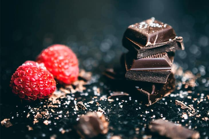 Dark chocolate pieces stacked with salt and raspberries