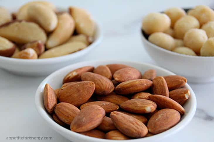 almonds, brazil nuts and macadamia nuts in white bowls