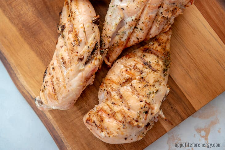 Keto stuffed Chicken removed from grill on wooden board