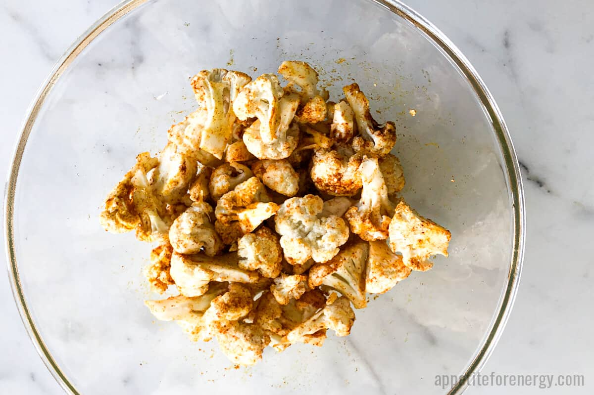 Cauliflower florets tossed with spices in glass bowl before roasting