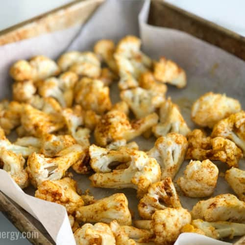 Cauliflower tossed in spices and oil, ready to roast in baking tray