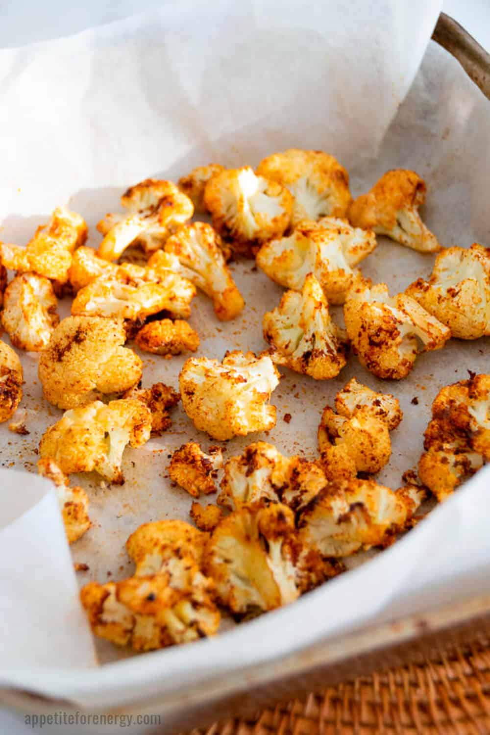 Close up of golden brown, spicy roasted cauliflower in a baking tray with parchment paper