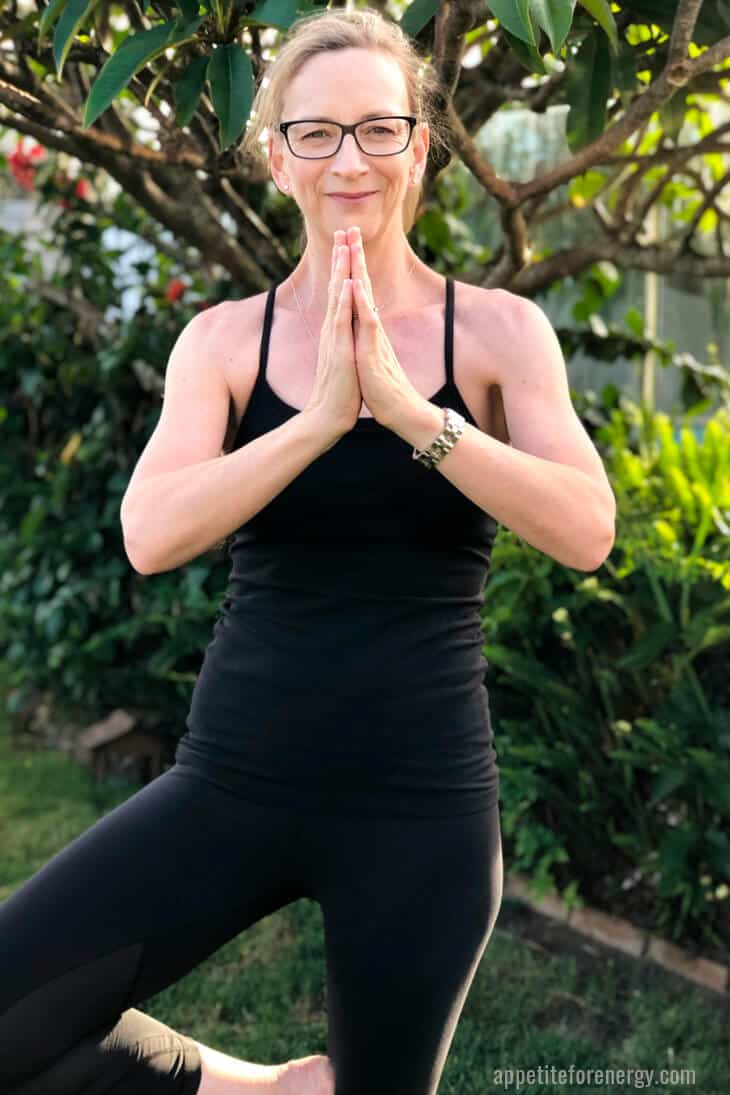 Anna Mazlin standing outside in blacl workout gear, in tree pose