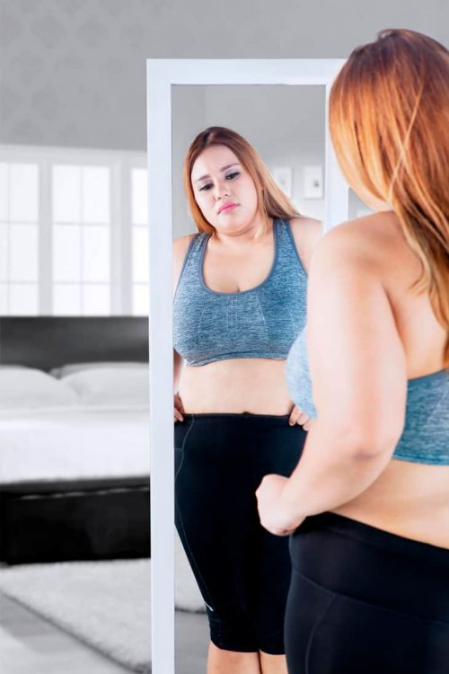 Woman looking sadly in mirror at stomach